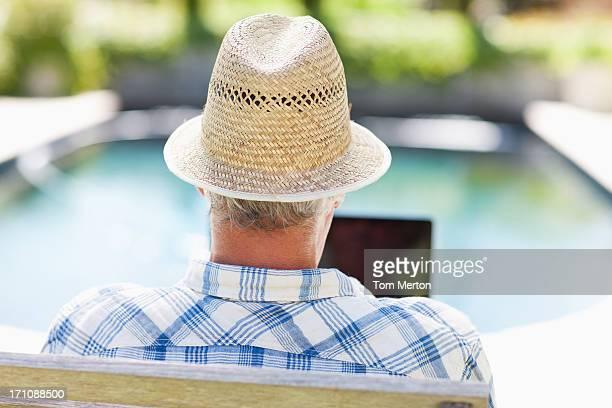 Alter Mann mit laptop am Pool