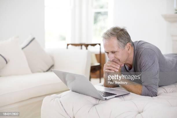 Senior man using laptop in livingroom