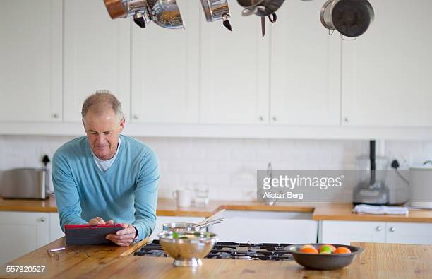 Senior man using tablet computer at home