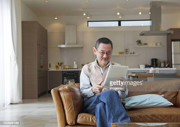 Senior man using tablet PC on a sofa