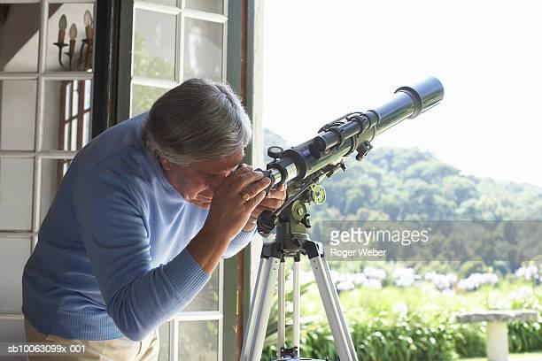 Senior man using telescope at home