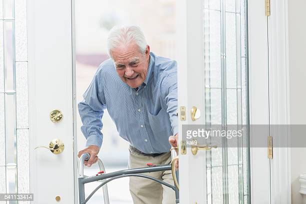 Senior man using walker, coming home through front door