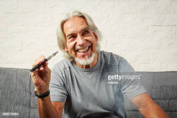 Senior man vaping, enjoying an electronic cigarette
