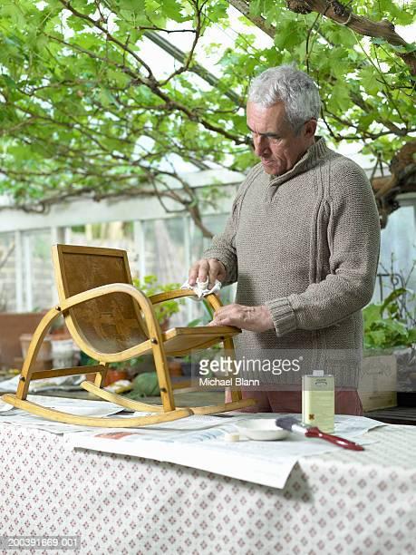 Senior man varnishing chair in greenhouse