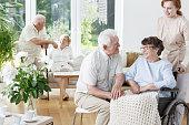 Senior man visits his smiling wife on wheelchair at friendly senior home
