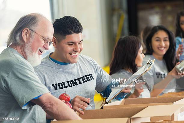 Senior man volunteering with younger adults in food bank