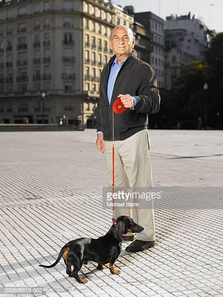 Senior man walking dog in town square, portrait