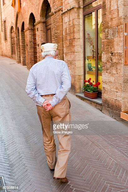 Senior man walking in a street, San Gimignano, Siena Province, Tuscany, Italy
