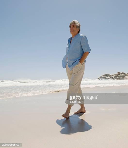 Senior man walking on beach, low angle view
