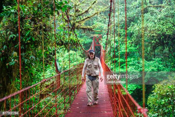 Senior man walking on suspension bridge in Monteverde Cloud forest , Costa Rica
