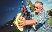 Washing car. Senior man polishing his car with microfiber cloth