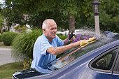 Senior man washing his car at home