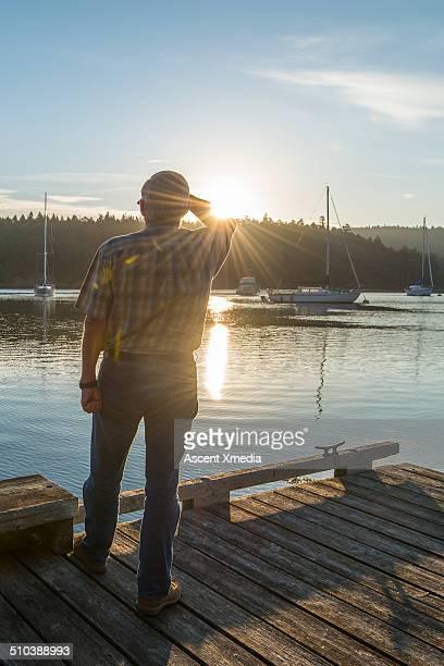 Senior man watches sunrise from wooden pier,marina