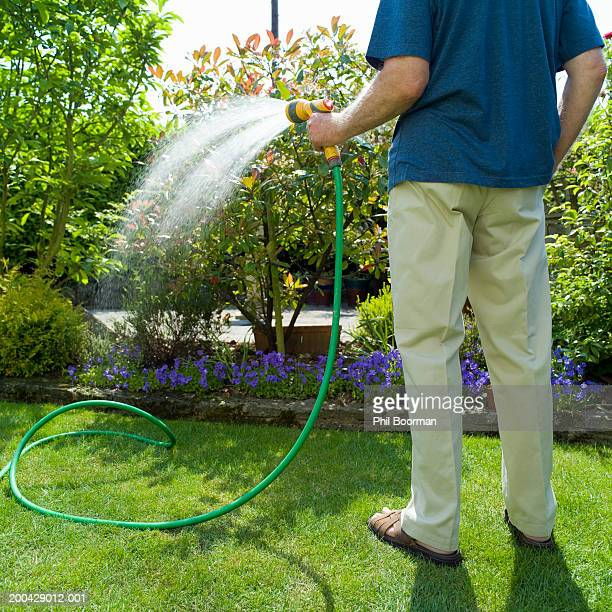 Senior man watering garden with hose, rear view