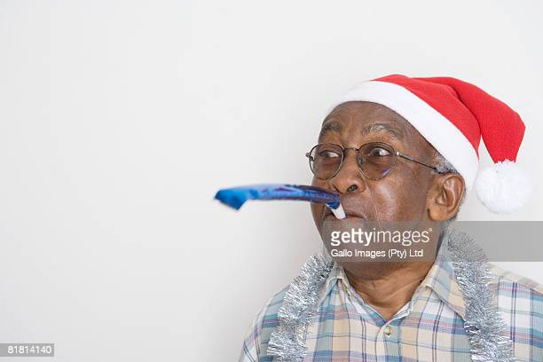 Senior man wearing a Christmas hat blowing a noise maker.