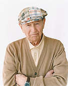 Senior Man Wearing a Flat Cap Standing With His Arms Crossed