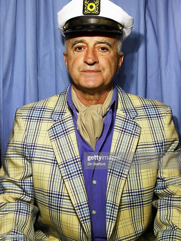 Senior man wearing blazer and cap in photo booth
