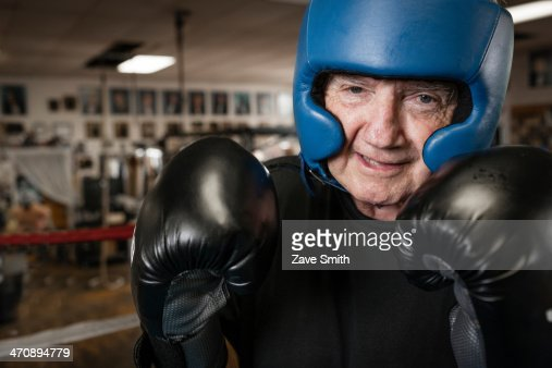 Senior man wearing boxing gloves and helmet