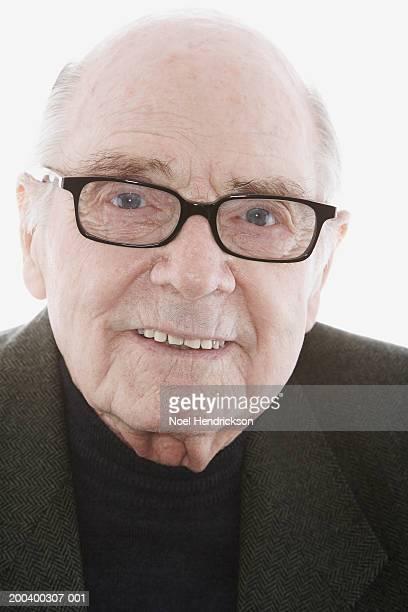 Senior man wearing glasses, smiling, portrait