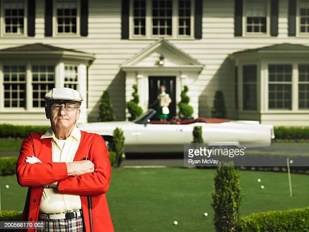 Senior man wearing golfing clothes standing in front garden, portrait