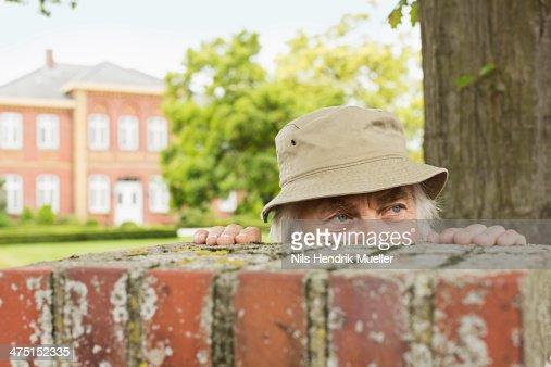 Senior man wearing hat peering over garden wall