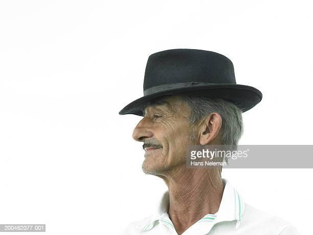 Senior man wearing hat, side view, close-up
