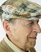 Senior man wearing hat, smiling, close-up