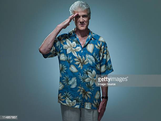 Senior man wearing hawaiian shirt saluting, portrait