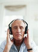 Senior man wearing headphones, eyes closed, close-up