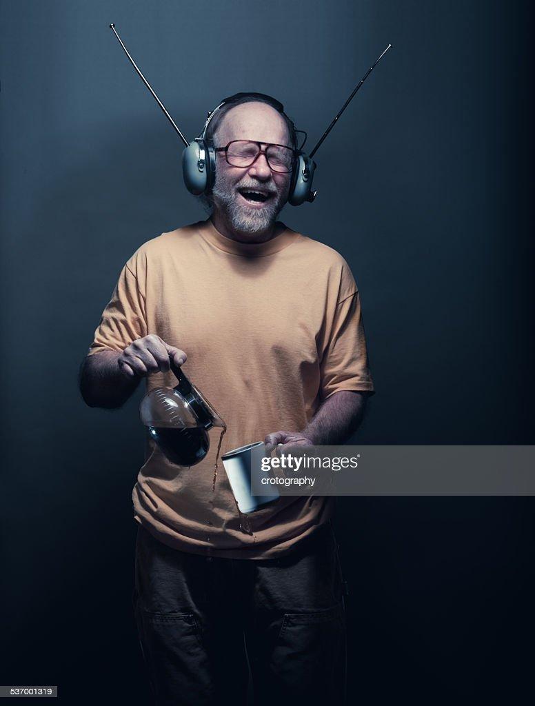 Senior man wearing headphones, singing and pouring tea