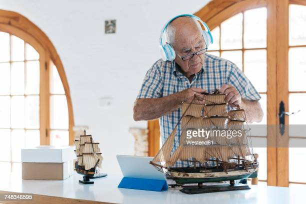 Senior man wearing headphones working on model ship on table with tablet
