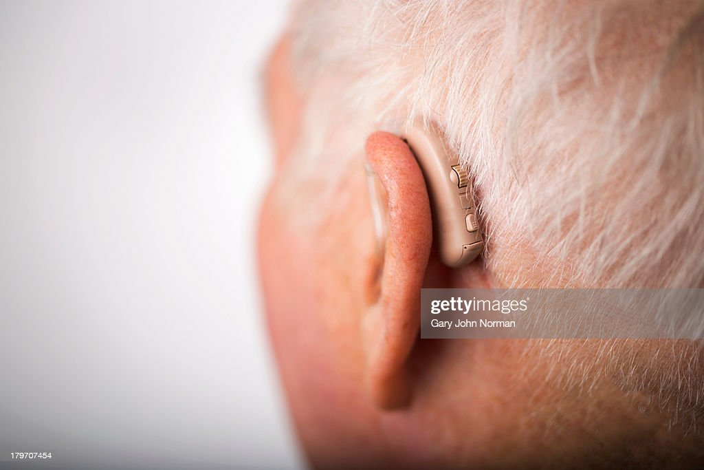 Senior man wearing hearing aid, close up