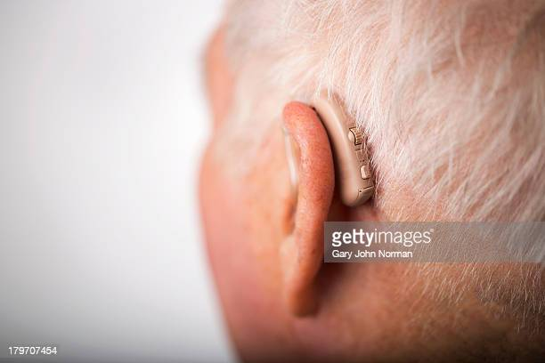 Senior man wearing hearing aid, close up