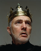 Senior man wearing king's crown, and looking away
