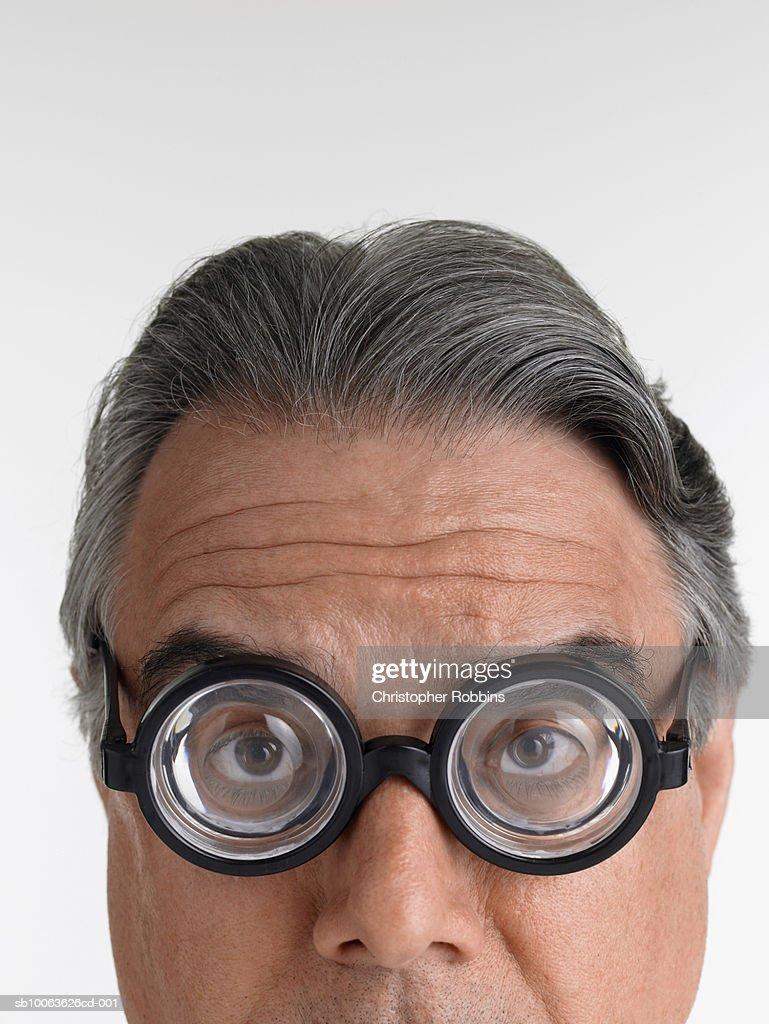 Senior man wearing novelty glasses, portrait, close-up