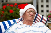 Senior man wearing Santa hat, dormir al aire libre