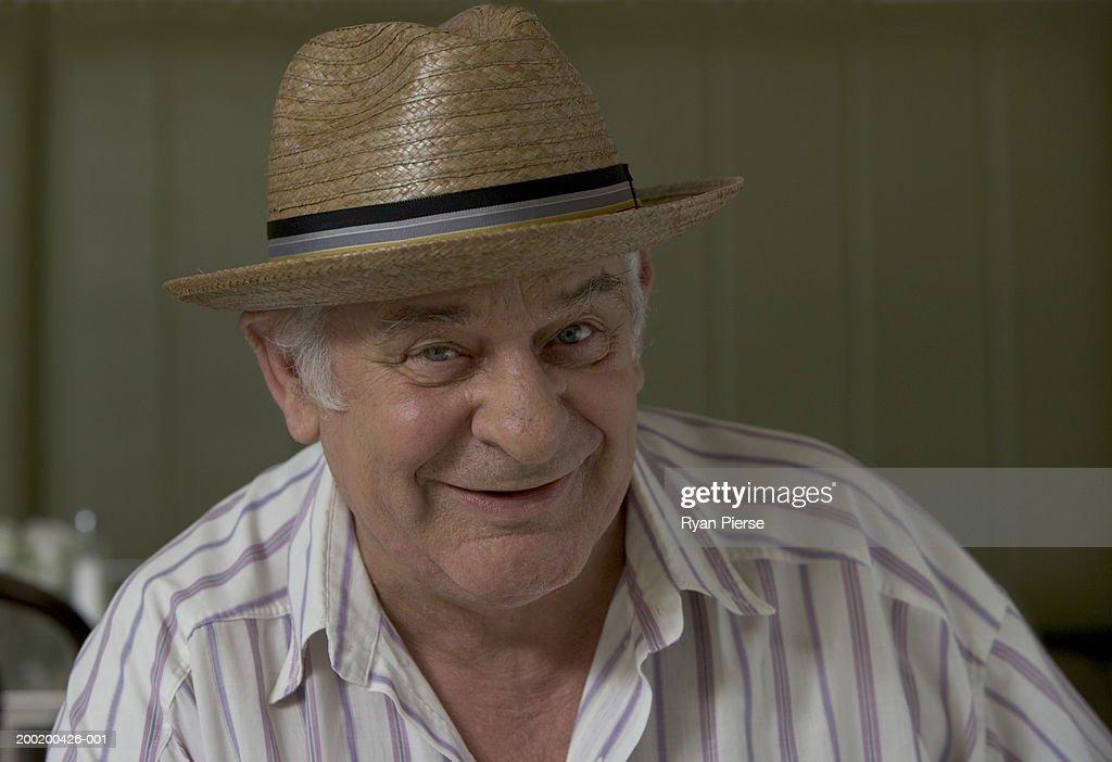 Senior man wearing straw hat, smiling, close-up, portrait
