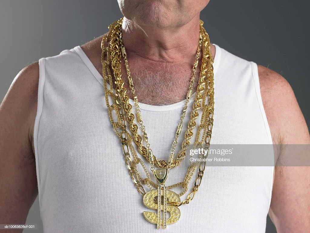 Senior man wearing tank top and gold chains with dollar sign, mid section : Stock Photo