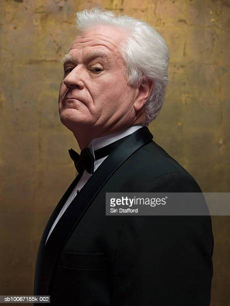 Senior man wearing tuxedo, portrait, side view, studio shot