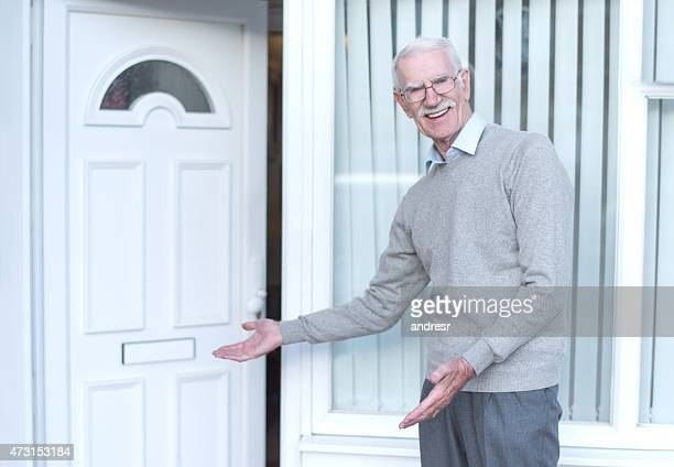 Senior man welcoming people to his house