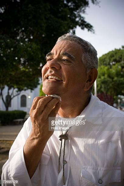 Senior man wiping face, outdoors