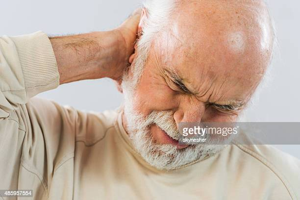 Homem idoso com uma dor de cabeça.