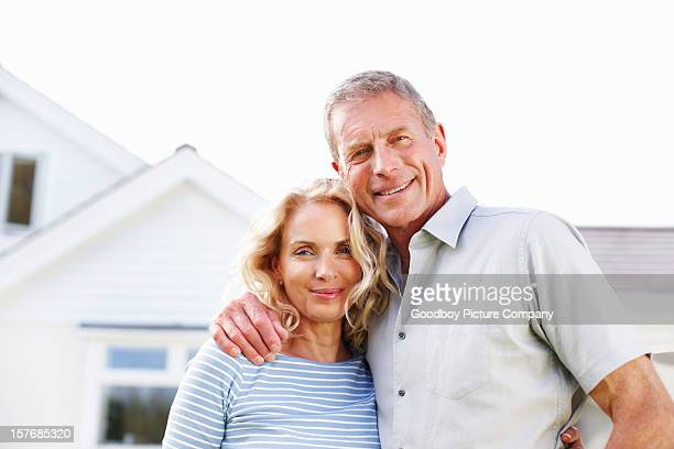 Senior man with a mature woman in front of house
