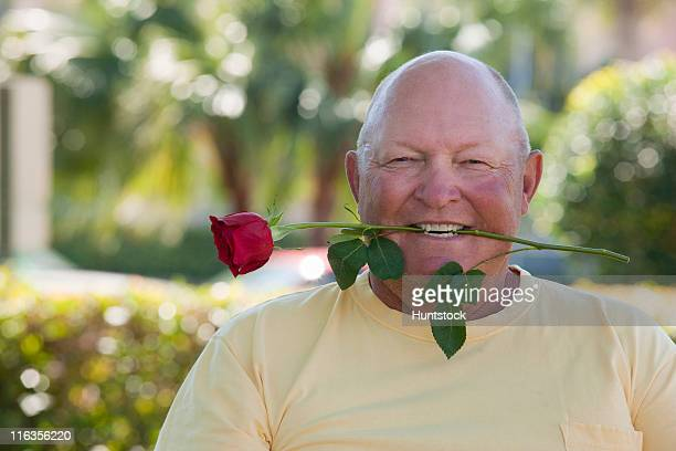 Senior man with a rose in his mouth