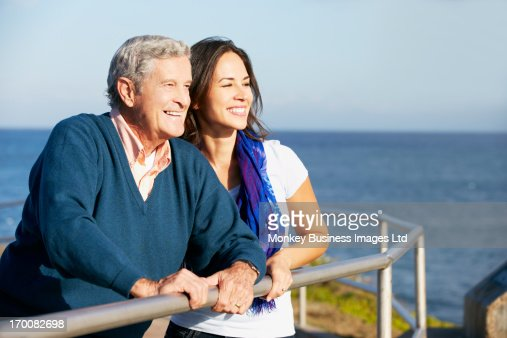Senior Man With Adult Daughter Looking Over Railing At Sea : Stock Photo