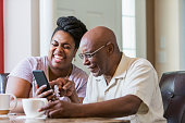 A senior African-American man in his 60s sitting at home with adult daughter, in her 30s at the dining room table, drinking coffee. The woman is showing her father something on her mobile phone and th