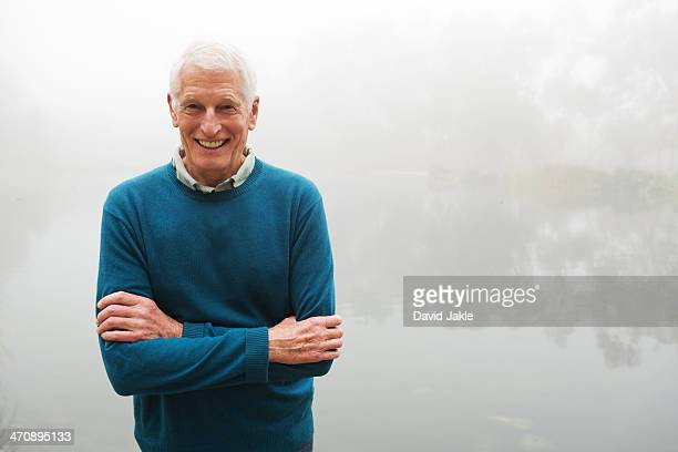 Senior man with arms crossed by foggy lake