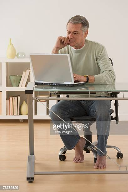Senior man with bare feet looking at laptop