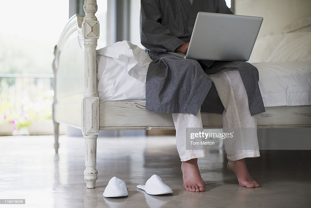 Senior man with bare feet sitting on edge of bed using laptop : Foto stock