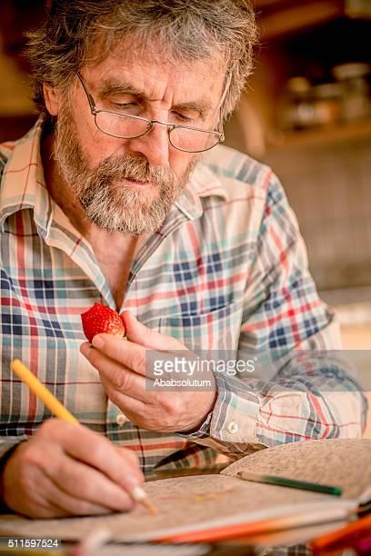 Senior homme avec barbe livre de coloriage et manger une fraise, l'Europe